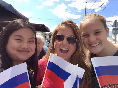 Students on the 2015 UGA Study Abroad program in Russia at a market, holding Russian flags